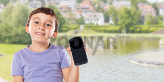 Cute boy child holding smartphone smart cell phone town banner copyspace copy space cellphone marketing ad advertising