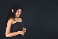 Young beautiful woman portrait listening modern music in headphone isolated over dark gray wide background