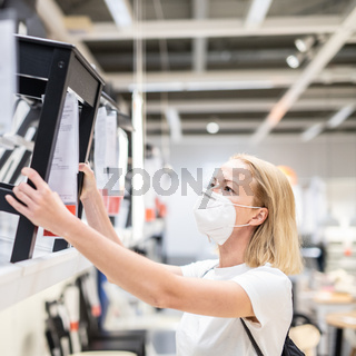 New normal during covid epidemic. Caucasian woman shopping at retail furniture and home accessories store wearing protective medical face mask to prevent spreading of corona virus
