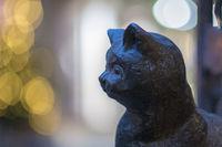 Portrait eines schwarzen Katzenkopfes aus Gusseisen vor unscharfem hellen Hintergrund