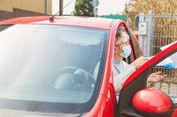 Seniorin mit Mundschutz als Autofahrer bei Coronavirus Pandemie