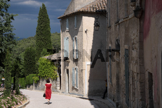 Woman with red dress in the old town of Oppede-le-Vieux