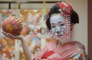 Maiko in kimono holding a temari ball in the hand.