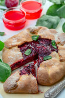 Open curd pastry pie with red plums.