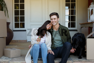 Smiling caucasian couple holding keys sitting outside house with dog