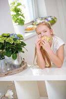 Kind isst ein belegtes Brötchen in der Küche