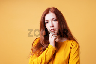 thoughtful young woman with finger on chin gesture