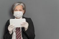 Gray-haired businesswoman works notepad. Caucasian lady holds tablet looking at camera on gray background with textspace on right. Focus on female face in protective mask. Virus outbreak concept