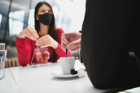 couple with protective medical mask  having coffee break in a restaurant