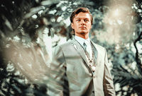 Handsome young man in classic suit posing on nature. Young attractive groom photo shooting enjoy photo session outdoors. Beauty and fashion photography concept