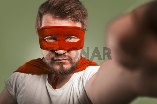Super hero man makes selfie photos or video by mobile phones. Serious man wearing red mask and cloak posing for his social networks followers. Isolated on green background