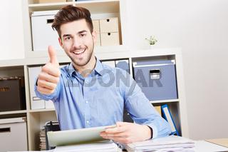 Mann mit Tablet Computer im Büro hält Daumen hoch