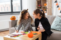 girls in halloween costumes doing crafts at home