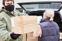 Lieferdienst Team mit Mundschutz liefert Pakete aus