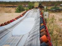 Blick über ein Förderband zum Transport von Kies in einer Kiesgrube.