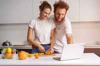 Man leaned on girl smiling watching romantic movie. Beautiful young couple talking on video call using laptop. Young couple cooking healthy food in kitchen at home