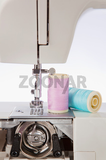 Sewing threads in pastel colors and Detailed view of a sewing machine