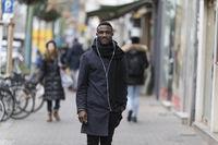 Young Man with Earphones Posing on Sidewalk