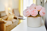 Pretty pink colour peonies flowers in white vase inside of light warm living room, selective close up focus on bouquet, no people. Concept of modern cozy residential flat interior detail decoration
