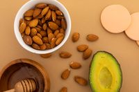 Avocado and bowls of almonds and salad ingredients on orange background