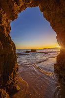 Blick vom Strand durch eine Felsformation auf den Atlantik, Sonnenuntergang an der Algarve, Portugal