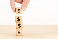 Growth, savings, wealth or richness concept. Hand holding a wooden block and blocks stacked with dollar symbol