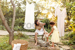 Mother and daughter hanging laundry in backyard