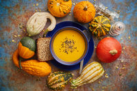 Compositon with autumn classic food. Tasty homemade pumpkin soup decorated with black seed