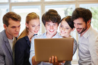 Junges Business Team schaut auf Laptop Computer
