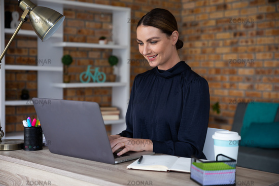Woman using laptop while sitting on her desk