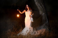 Scary woman with a lantern in night scene - Spooky image of a scary woman with dark eyes and appearance of a witch, in a white dress, holding a lit lantern and a frightening doll, in a dark night atmosphere.
