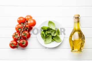 Cherry tomatoes, basil leaves and olive oil in bottle.