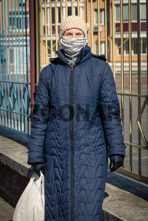 A poor elderly woman wears a homemade mask to protect herself from viruses
