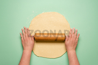 Making a pie top view. Woman stretching the dough on green table