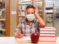 Hispanic Boy Wearing Face mask with Books, Apple, Pencil and Paper at Library