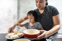 Asian girl cooking with mom