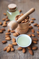almonds oil and nuts on a wooden background