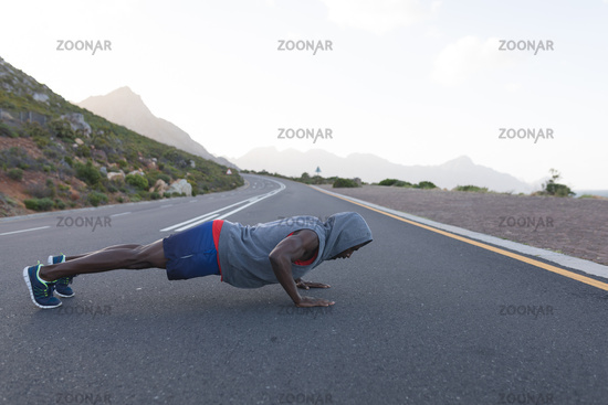 Fit african american man in sportswear doing push ups on a coastal road