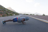 Fit african american man in sportswear doing push ups on a coastal road