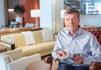 Senior man facing camera and holding US dollar bills as though handing to viewer