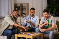 happy male friends playing cards at home at night