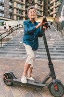 Active old woman riding electric scooter. Retired lady uses environmentally friendly city vehicle. Granny very old with gray hair, active and progressive. Modern senior woman use technology e scooter