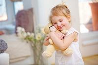 Kind kuschelt mit weichem Kuscheltier