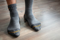 male feet in grey socks on a wooden floor