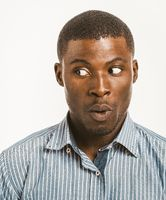 Young dark-skinned man makes surprised face looking to the left at copy space. Surprised African American male head shoulders portrait on white background. Close up shot. Toned image