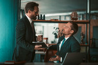 Two colleagues in the office are having a discussion. Men in business suits. One sits at a desk with a laptop. The second man is standing next to the notebook. High quality photo