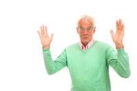 Senior man in green jumper surprised