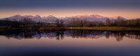 autumn pond with the reflection of the mountains on the surface at sunset