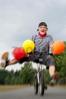Mann mit vielen Luftballons und Kinderfahrrad