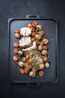 Traditional barbecue rolled lamb roast sliced with tomatoes and mini eggplant as top view on a modern design black tray